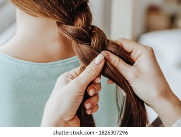Two girls braid their hair at the window. Woman makes a braid to her friend. Hair weaving hairstyles. Girlfriend braids her hands with ringlets. Hair care