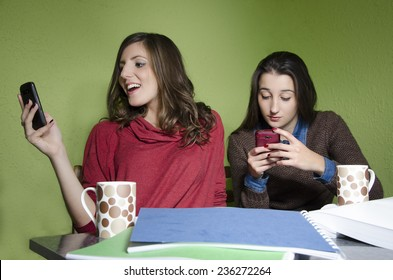 Two girls browsing internet via smart phones, while studying. Trying to solve a problem using the internet /technology, selective focus on girl in red
