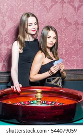 Two girls in casino with card batch