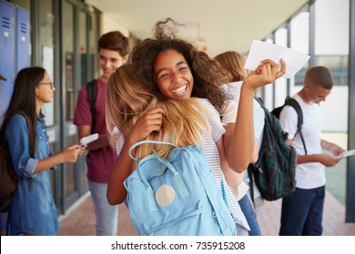 Two girls celebrating exam results in school corridor