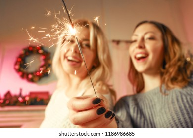 Two girls celebrating new year at home. Young laughing women holding bengal lights