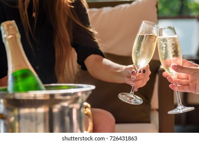 two girls clink glasses of champagne on a beautiful summer terrace. sparkling champagne glasses. close up