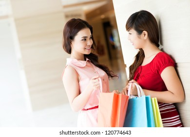Two girls communicating in store and showing purchases