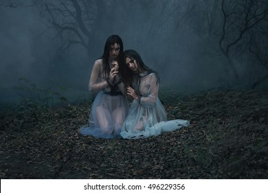 Two girls cry. Young ladies in vintage dresses sitting on the sinister a forest glade waiting for his victim. Photo shoot in the style of horror. Mystical photo. Fashion toning.Creative color.
