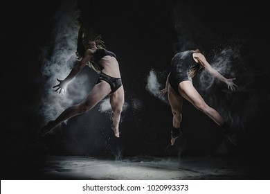 Two girls dance with flour in studio on black background, lights behind them and people helped girls with flour