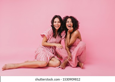two girls with dark hair, one with straight and other with curly, dressed in soft and lovely pajamas, having fun and playing, looking at camera