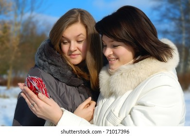 Two girls with a decorative heart in winter