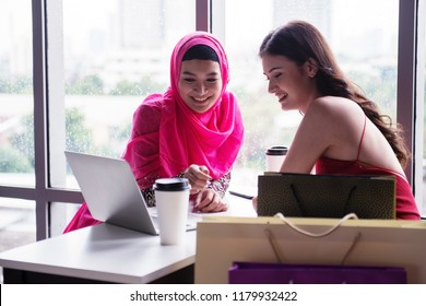 Two girls different culture are talking about business. They look happy together. Islam girl in this pink Hijab and dress make her look beautiful. And girl in red dress looks very elegant.