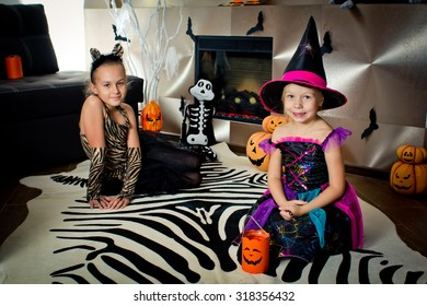 Two girls disguised as a tiger and as a witch are waiting for some candies in All Saints' Day. Halloween at home.