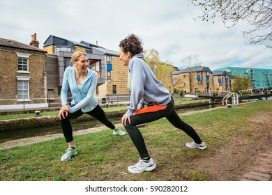 Two girls doing stretching exercises outdoors in London