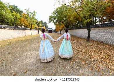 Two girls dressed in traditional Korean Hanbok dress enjoying autumn scenery within Geyongbokgung Palace grounds