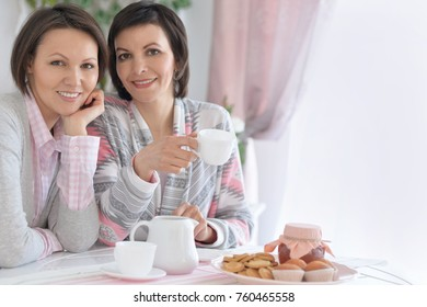 two girls are drinking tea