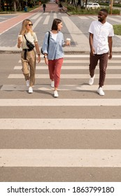 Two girls with drinks talking to African guy in casualwear while crossing road and walking to other side of street after visiting large park