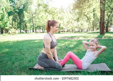 Two girls are excercising in park. Woman is sitting on her knees and holding her daughter's feet while small girl is doing some abs excercises. Yoga and Pilates Concept