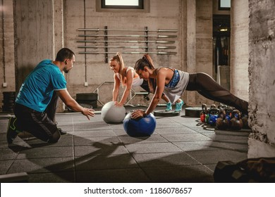 Two girls exercising with a personal trainer at the gym.