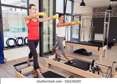 Two girls are exercising pilates using weights