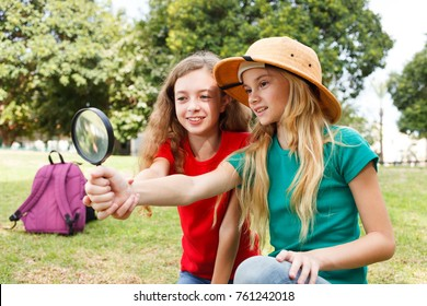Two girls exploring the nature with magnifying glass
