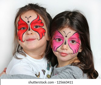 Two girls with face painting of a butterfly.