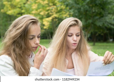 Two girls are female students, write homework instead of me. Portrait of bored younger sister in park