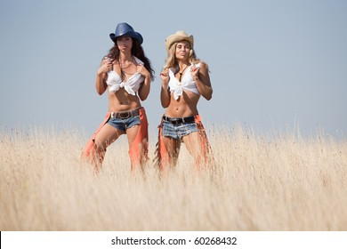 Two girls at the field. Young women in costumes of cowboys outdoors