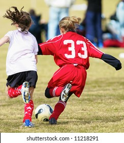 Two girls fighting for the soccer ball during a game