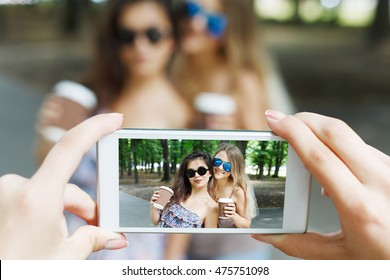 Two girls friends with coffee take away outdoors and someone POV view, taking photos at digital camera of smartphone. Young females at mobile screen, having fun in summer park. Lifestyle portrait.