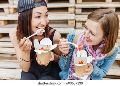 two girls friends enjoying a chinese take away wok noodle food in the street.