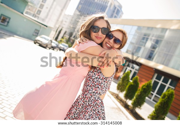 two girls friends laughing and hugging. hug and smile outdoor