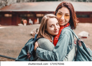 Two girls friends of a student walk around the zoo and watch the animals