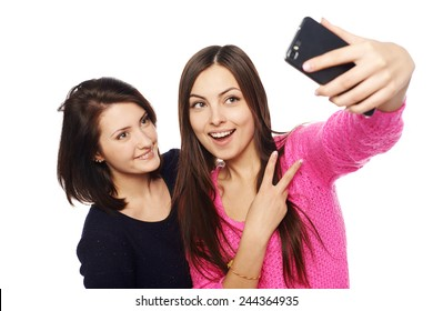 Two girls friends taking selfie with smartphone, isolated on white background