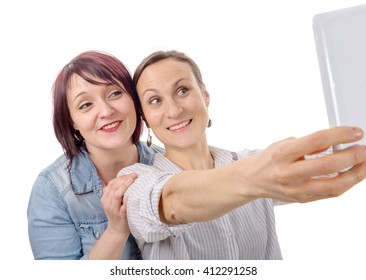 Two girls friends taking selfie with digital tablet, isolated on white background