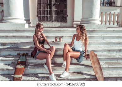 Two girls girlfriends, summer city, skate boards, longboard cups coffee tea. They talk relaxed communicate long hair tanned figure. Background steps building column. Fashion style, modern lifestyle