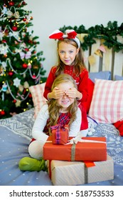 Two girls give gifts near a Christmas tree in rabbit ears near the bed