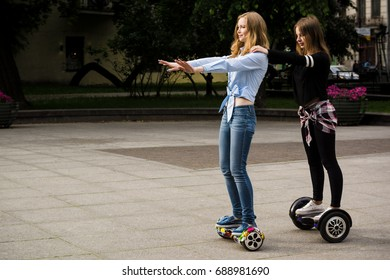 Two girls go on hoverboards one after another. Brunette and blonde on a hoverboard.