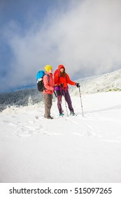 Two girls go on a snowy hill during a mountaineering adventure in the mountains.