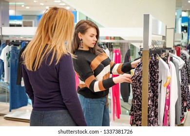 Two girls go shopping, choose clothes in the store