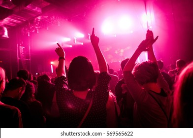 Two girls with hands up at a concert in the music club