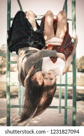 Two girls hang on a horizontal bar in an embrace. The concept of difficult teenagers, bad students. Representatives of youth subcultures.