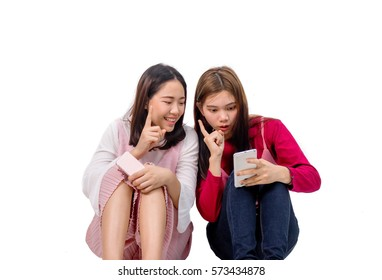 Two girls are happily doing FaceTime with some one on the mobile phone.