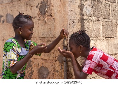 Two Girls Happily Sharing Water from tap in Bamako, Mali