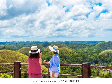 Two girls in hats on the background of the Chocolate hills, Bohol island, Philippines. With selective focus
