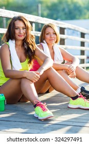 Two girls have a rest after exercising outdoors