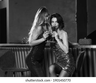 Two girls having fun in bar. Elegant woman in fahionable sequins dresses. Nightclub party. Female celebrating, having fun in bar. Beautiful caucasian blonde and brunette ladies