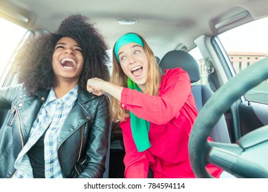two girls having fun in car. concept of diversity and friendship.
