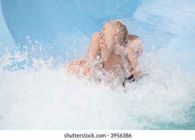 two girls having fun coming down a waterslide
