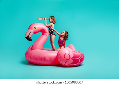 Two girls having fun on inflatable toy flamingo. Children in swimsuits with one holding a toy binoculars and other pointing at something interesting while playing on mattress over blue background.