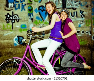 two girls having fun on a bicycle, personal editing ,green toning
