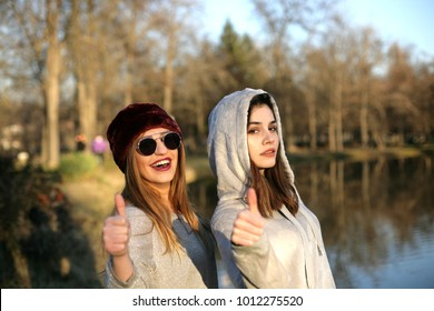 Two girls having fun in a park; two girls looking in camera and showing their thumbs up.