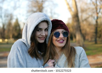 Two girls having fun in a park; portrait of two fashionable young women in nature.