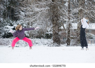 Two girls having a snowball fight